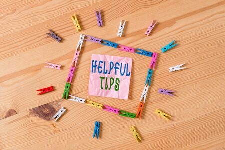 Text sign showing Helpful Tips. Business photo showcasing Ask an Expert Solutions Hints Consulting Warning Colored clothespin papers empty reminder wooden floor background office