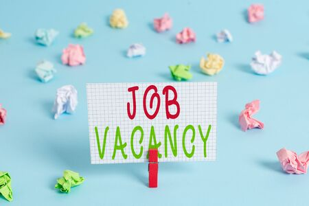 Conceptual hand writing showing Job Vacancy. Concept meaning empty or available paid place in small or big company Colored clothespin rectangle shaped paper blue background