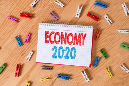 Conceptual hand writing showing Economy 2020. Concept meaning State of wealth and resources of a country in upcoming year Colored crumpled papers wooden floor background clothespin