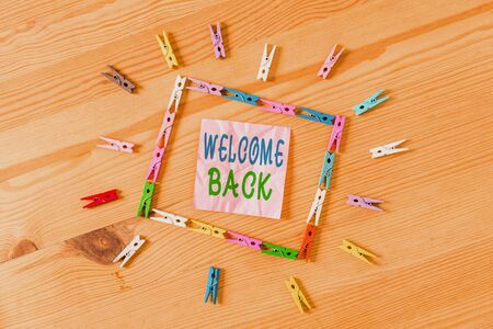 Text sign showing Welcome Back. Business photo showcasing Warm Greetings Arrived Repeat Gladly Accepted Pleased Colored clothespin papers empty reminder wooden floor background office