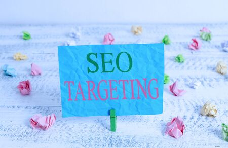Word writing text Seo Targeting. Business photo showcasing Specific Keywords for Location Landing Page Top Domain Green clothespin white wood background colored paper reminder office supply 写真素材