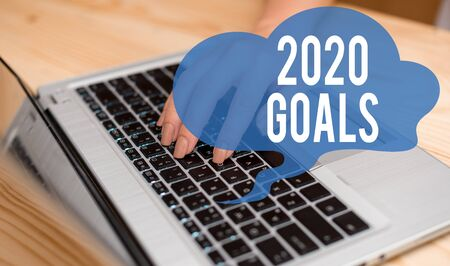 Conceptual hand writing showing 2020 Goals. Concept meaning A plan to do for something new and better for the coming year woman with laptop smartphone and office supplies technology 스톡 콘텐츠