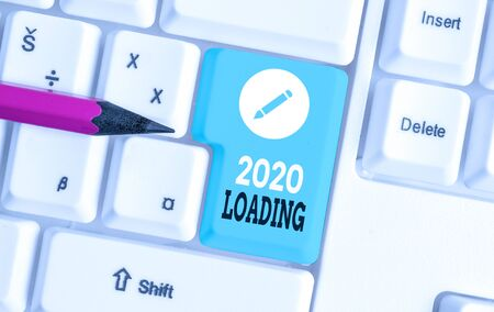Word writing text 2020 Loading. Business photo showcasing Advertising the upcoming year Forecasting the future event White pc keyboard with empty note paper above white background key copy space