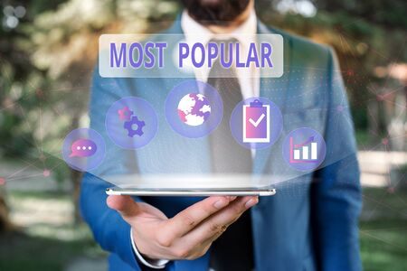 Handwriting text Most Popular. Conceptual photo Liked Followed Enjoyed by majority of the showing in a society Male human wear formal work suit presenting presentation using smart device 스톡 콘텐츠
