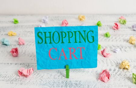 Word writing text Shopping Cart. Business photo showcasing Case Trolley Carrying Groceries and Merchandise Green clothespin white wood background colored paper reminder office supply