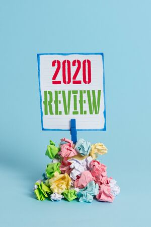 Word writing text 2020 Review. Business photo showcasing seeing important events or actions that made previous year Reminder pile colored crumpled paper clothespin reminder blue background 스톡 콘텐츠