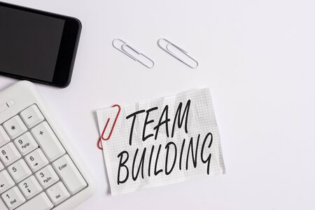 Text sign showing Team Building. Business photo showcasing Types of activities used to enhance social relations White pc keyboard with empty note paper above white background and mobile phone