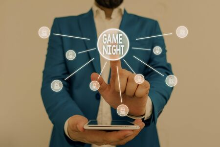 Text sign showing Game Night. Business photo showcasing event in which folks get together for the purpose of getting laid Male human wear formal work suit presenting presentation using smart device