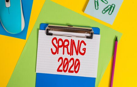 Word writing text Spring 2020. Business photo showcasing time of year where flowers rise following winter season Clipboard striped sheets marker clips notepad mouse colored background