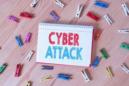Conceptual hand writing showing Cyber Attack. Concept meaning An attempt by hackers to Damage Destroy a Computer System Colored crumpled papers wooden floor background clothespin