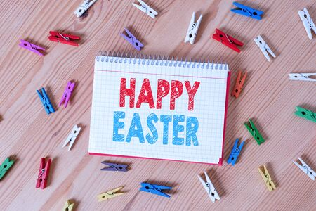 Conceptual hand writing showing Happy Easter. Concept meaning Christian feast commemorating the resurrection of Jesus Colored crumpled papers wooden floor background clothespin Фото со стока