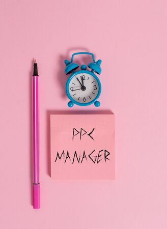 Text sign showing Ppc Manager. Business photo text which advertisers pay fee each time one of their ads is clicked Metal vintage alarm clock wakeup blank notepad marker colored background