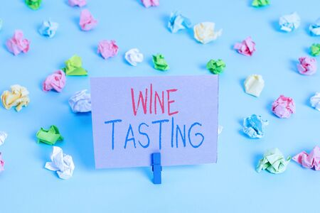 Word writing text Wine Tasting. Business photo showcasing Degustation Alcohol Social gathering Gourmet Winery Drinking Colored crumpled papers empty reminder blue floor background clothespin