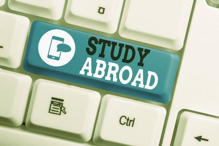 Conceptual hand writing showing Study Abroad. Concept meaning Pursuing educational opportunities in a foreign country Keyboard with note paper on white background key copy space Фото со стока - 130158117