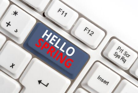 Writing note showing Hello Spring. Business concept for Welcoming the season after the winter Blossoming of flowers White pc keyboard with note paper above the white background