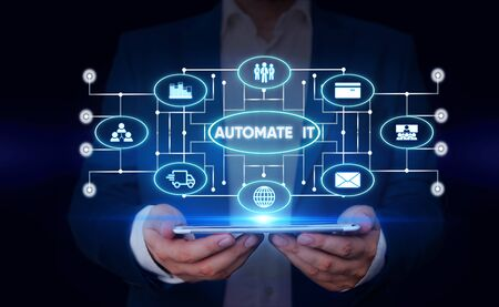 Writing note showing Automate It. Business concept for convert process or facility to be operated automatic equipment. Male wear formal suit presenting presentation smart device Stockfoto