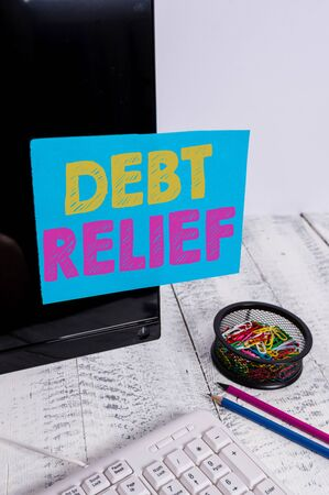 Writing note showing Debt Relief. Business concept for partial or total remission of it especially those by countries Note paper taped to black computer screen near keyboard and stationary Stock fotó