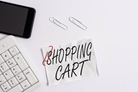 Text sign showing Shopping Cart. Business photo showcasing Case Trolley Carrying Groceries and Merchandise White pc keyboard with empty note paper above white background and mobile phone Foto de archivo - 130156725