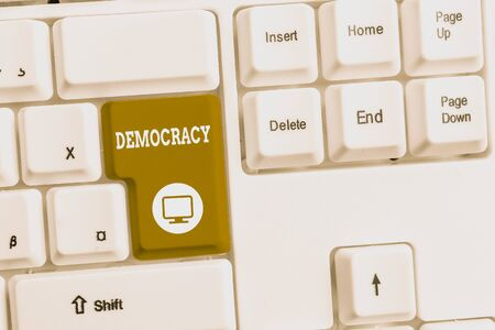 Text sign showing Democracy. Business photo text freedom of the showing to express their feelings and beliefs White pc keyboard with empty note paper above white background key copy space Stock fotó