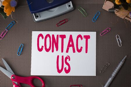 Handwriting text Contact Us. Conceptual photo Group of demonstrating that rendering costumer service through telecom Scissors and writing equipments plus plain sheet above textured backdrop