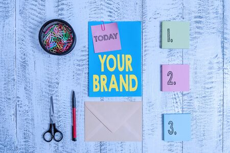 Word writing text Your Brand. Business photo showcasing A name of any kind that is impacted to something as trademark Envelope letter sticky note ballpoint clips can scissors wooden background