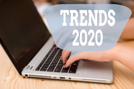 Conceptual hand writing showing Trends 2020. Concept meaning Upcoming year prevailing tendency Widely Discussed Online woman with laptop smartphone and office supplies technology Stock Photo