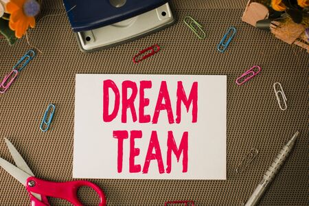 Handwriting text Dream Team. Conceptual photo Prefered unit or group that make the best out of a demonstrating Scissors and writing equipments plus plain sheet above textured backdrop