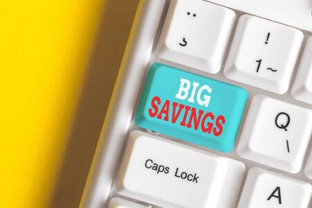 Writing note showing Big Savings. Business concept for income not spent or deferred consumption putting money aside White pc keyboard with note paper above the white background 写真素材