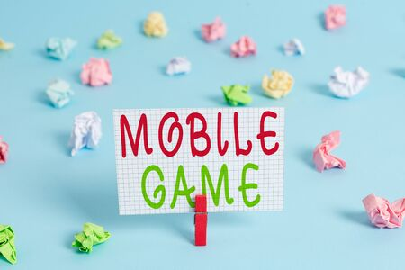 Conceptual hand writing showing Mobile Game. Concept meaning they are entertaining programs made to work on smart device Colored clothespin rectangle shaped paper blue background Stock fotó