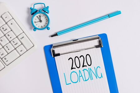 Conceptual hand writing showing 2020 Loading. Concept meaning Advertising the upcoming year Forecasting the future event Flat lay above table with clock pc keyboard and note paper