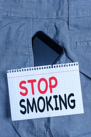 Handwriting text Stop Smoking. Conceptual photo Discontinuing or stopping the use of tobacco addiction Smartphone device inside formal work trousers front pocket near note paper