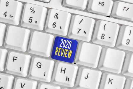 Conceptual hand writing showing 2020 Review. Concept meaning seeing important events or actions that made previous year White pc keyboard with note paper above the white background 스톡 콘텐츠