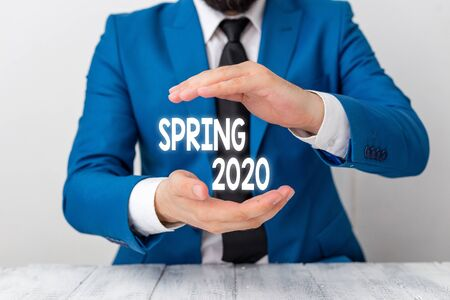 Writing note showing Spring 2020. Business concept for time of year where flowers rise following winter season Man holds empty paper with copy space in front of him Space