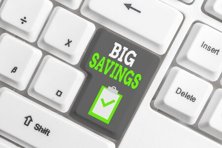 Handwriting text writing Big Savings. Conceptual photo income not spent or deferred consumption putting money aside White pc keyboard with empty note paper above white background key copy space