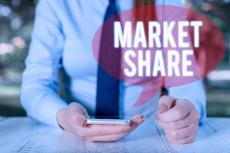 Writing note showing Market Share. Business concept for The portion of a market controlled by a particular company Female business person sitting by table and holding mobile phone