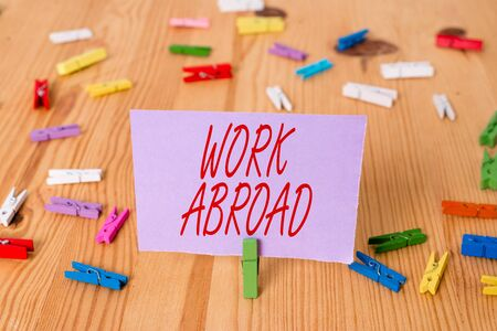Handwriting text Work Abroad. Conceptual photo Immersed in a foreign work environment Job Overseas Non Local Colored clothespin papers empty reminder wooden floor background office