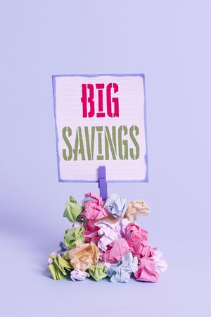 Word writing text Big Savings. Business photo showcasing income not spent or deferred consumption putting money aside Reminder pile colored crumpled paper clothespin reminder blue background 写真素材