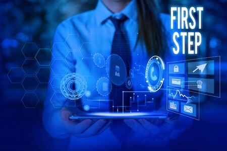 Writing note showing First Step. Business concept for Pertaining to the start of a certain process or beginning Woman wear formal work suit presenting presentation using smart device