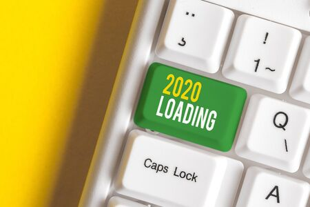Handwriting text writing 2020 Loading. Conceptual photo Advertising the upcoming year Forecasting the future event White pc keyboard with empty note paper above white background key copy space