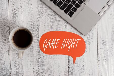 Word writing text Game Night. Business photo showcasing event in which folks get together for the purpose of getting laid Trendy metallic open laptop speech bubble vintage wooden table coffee cup