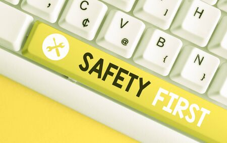 Conceptual hand writing showing Safety First. Concept meaning Avoid any unnecessary risk Live Safely Be Careful Pay attention White pc keyboard with note paper above the white background