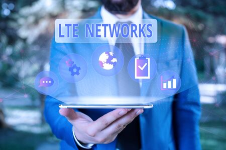Handwriting text Lte Networks. Conceptual photo Fastest network connection available for wireless communication Male human wear formal work suit presenting presentation using smart device Foto de archivo