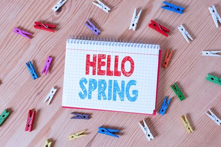 Conceptual hand writing showing Hello Spring. Concept meaning Welcoming the season after the winter Blossoming of flowers Colored crumpled papers wooden floor background clothespin Zdjęcie Seryjne - 130154970