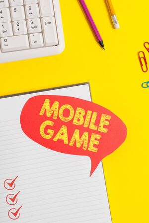 Text sign showing Mobile Game. Business photo showcasing they are entertaining programs made to work on smart device Pink empty paper on the yellow table with pencil