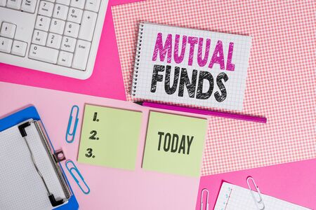 Text sign showing Mutual Funds. Business photo text An investment program funded by shareholders Individual Stocks Writing equipments and computer stuffs placed above colored plain table