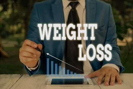 Handwriting text writing Weight Loss. Conceptual photo Decrease in Body Fluid Muscle Mass Reduce Fat Dispose Tissue Male human wear formal work suit presenting presentation using smart device