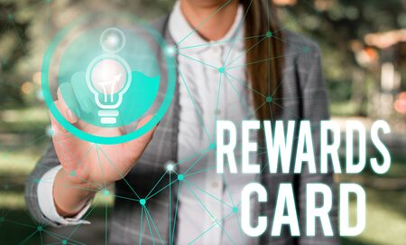 Handwriting text Rewards Card. Conceptual photo Help earn cash points miles from everyday purchase Incentives Female human wear formal work suit presenting presentation use smart device Stock Photo
