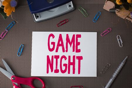 Handwriting text Game Night. Conceptual photo event in which folks get together for the purpose of getting laid Scissors and writing equipments plus plain sheet above textured backdrop