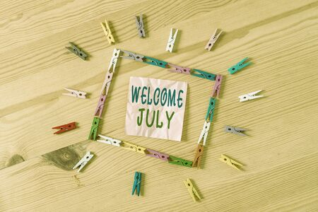 Text sign showing Welcome July. Business photo showcasing Calendar Seventh Month 31days Third Quarter New Season Colored clothespin papers empty reminder wooden floor background office