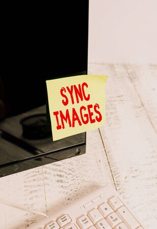 Word writing text Sync Images. Business photo showcasing Making photos identical in all devices Accessible anywhere Notation paper taped to black computer monitor screen near white keyboard